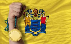 gold medal for sport and  flag of american state of new jersey - stock photo