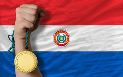 Stock Photo of gold medal for sport and  national flag of paraguay