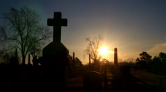 Man paying respect at cemetery cross silhouette Stock Footage
