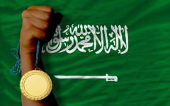 gold medal for sport and  national flag of  of saudi arabia - stock photo