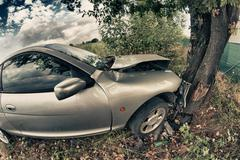 Broken Car After an Accident against a Tree - stock photo