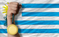gold medal for sport and  national flag of uruguay - stock photo