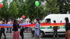 Gay parade walks street with long rainbow flag escorted police Stock Footage