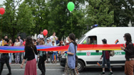 Stock Video Footage of gay parade walks street with long rainbow flag escorted police