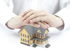 Hands and little yellow house - stock photo