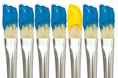 paint brushes with blue and yellow paints - stock photo