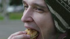 Young man eats hamburger from fast food and smiles on camera closeup Stock Footage