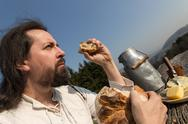 Stock Photo of rustically man with long hair eating bread in the nature