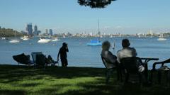 Pan of seniors sitting on chairs in park, matilda bay, perth, australia Stock Footage