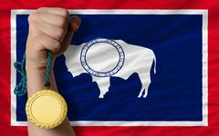gold medal for sport and  flag of american state of wyoming - stock photo