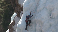 Female ice climber labors to scale ice wall. Stock Footage