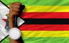 Stock Photo of silver medal for sport and  national flag of zimbabwe