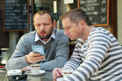 men using cellphone and sitting outside the cafe - stock footage