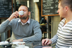 Men finishing coffee and leaving the table outside the cafe Stock Footage