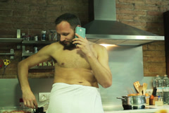 Man in a towel drinking coffee and standing in the kitchen Stock Footage