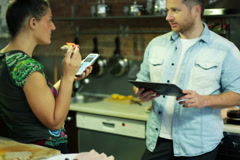 Young couple with cellphone and tablet talking and eating in the kitchen Stock Footage