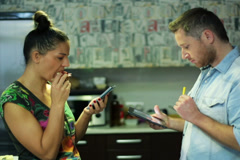 Couple eating and using cellphone and tablet in the kitchen Stock Footage