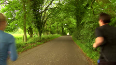 Man and woman jog past camera  down country lane Stock Footage