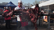 Stock Video Footage of Whole veal roasting on barbeque, chef cutting meat, barbeque, fair, market