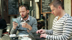 Men working on cellphone and laptop and sitting outside the cafe Stock Footage