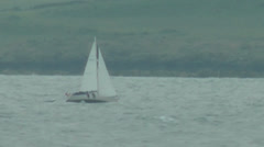 Sailing white yacht by coast, green hills in background Stock Footage