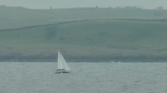 Sail Boat off coast with steep hills from sea Stock Footage