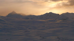 Rose Hued Clouds and Golden Rays over Stark Snowy Mountains Valhalla Stock Footage