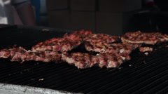 Cook turning, cutting pork meat on grill, barbecue, BBQ, street vendors, fair - stock footage