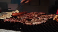 Stock Video Footage of Pork meat, sausages on grill, barbecue, BBQ, cooking, street vendors, fair