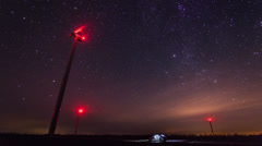 Wind turbines generating power at night timelapse with rotating starry sky on a - stock footage