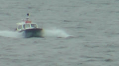 Small blue and white motor boat on choppy sea bouncing over waves - stock footage