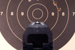 Pistol aimed at target - stock photo