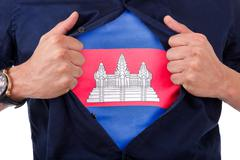 Young sport fan opening his shirt and showing the flag his country cambodia Stock Illustration