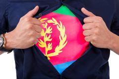 Young sport fan opening his shirt and showing the flag his country eritrea, e Stock Illustration