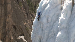 Male climber scales ice wall. Stock Footage