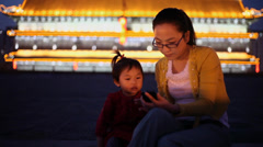 Stock Video Footage of Mother and daughter using mobile phone on xi'an city wall, Xi'an, China.