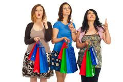 Amazed shoppers women looking up - stock photo