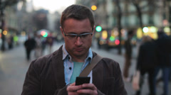 Man walking along the street and texting on his cellphone Stock Footage