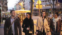 Friends walking on a pavement in the city at night Stock Footage