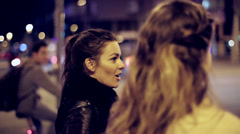 Girls chatting and waiting to cross the street in the city Stock Footage