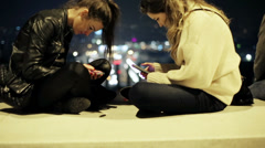 Two women sitting on a bench and using their cellphones Stock Footage