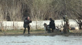 Two fishermen with  dog on  river bank are photographed. Footage