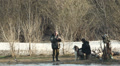Two fishermen with  dog on  river bank are photographed. HD Footage
