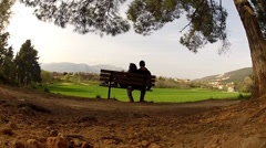 A loving couple is sitting on a bench and is enjoying the view. Stock Footage