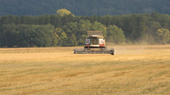 A combine harvester (header) harvesting an oats crop - stock footage