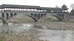 River flowing through a big stone arch bridge, Qionglai, Chengdu, Sichuan, China Stock Footage