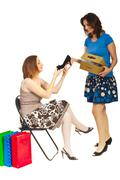 Smiling clerk showing new shoe to woman - stock photo
