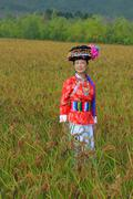Mosuo minority nationality girl in beautiful dress, stands in rice field - stock photo