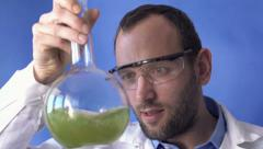 Stock Video Footage of Scientist mixing chemicals in cylindrical flask HD