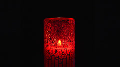 Candle burning in red holder Stock Footage